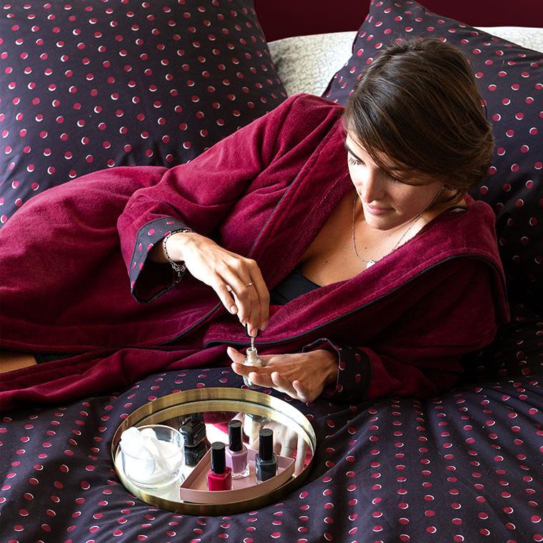 Femme en peignoir de velours rouge qui se met du vernis à ongles sur son lit pendant une soirée cocooning