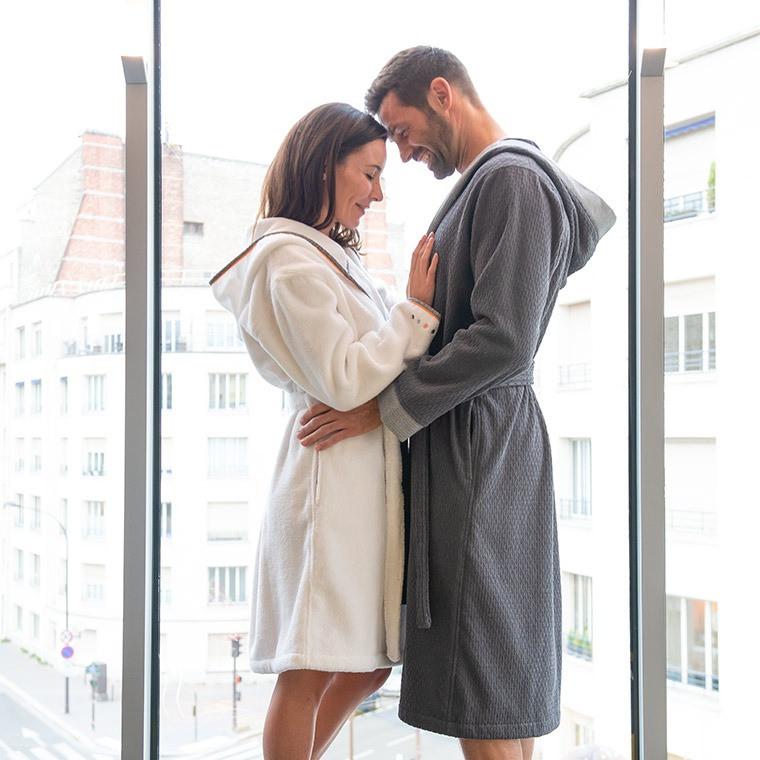 Jeune couple en peignoir de bain qui se câline devant une fenêtre